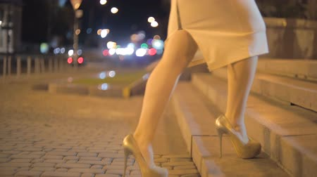 subir : Closeup shot of sexy woman in high heel shoes walking on stone stairs at night