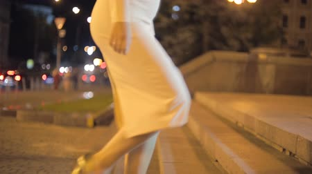 high heels : Closeup shot of sexy woman in dress walking on stairs at night