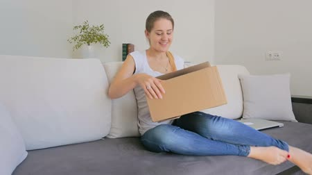 kutu : Happy young woman shopping online and unpacking parcel with new clothes