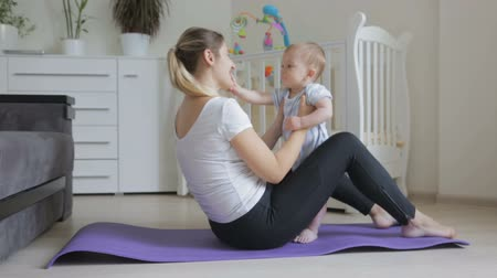 holding steady : Beautfiul young woman exercising on fitness mat holding her cute baby son