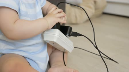 otřes : Closeup shot of little baby boy playing with charging wires and extension cable at home Dostupné videozáznamy