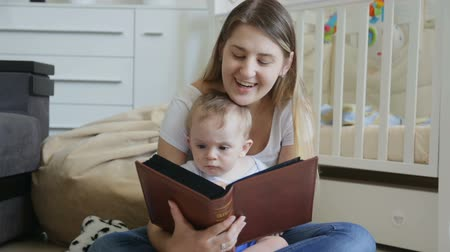 dizer : Happy young mother with baby boy reading big book on floor at living