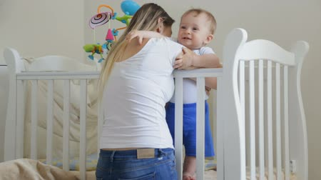 hozzábújva : Cute toddler boy laughing being tickled by his mother in the crib
