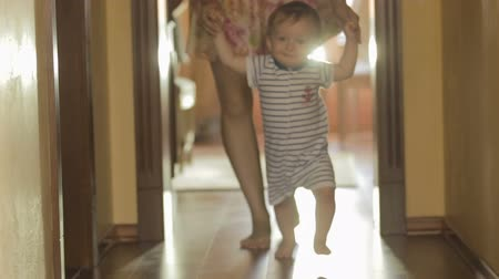 enseigner : Cute baby boy walking with mother on wooden floor at home Vidéos Libres De Droits