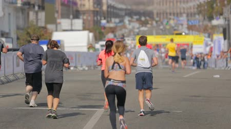 zadní : Rear view shot of  young woman running on city marathon day
