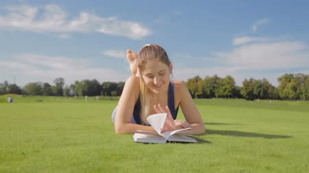 enciclopédia : Dolly shot of beautiful smiling woman lying on grass at park and reading a book