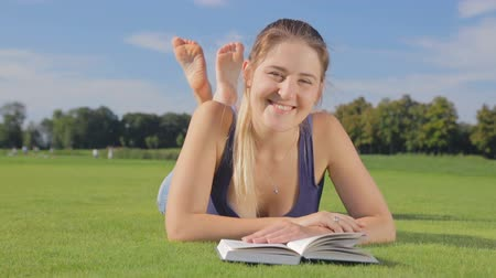 yatarken : Smiling young girl lying with book on grass at garden Stok Video