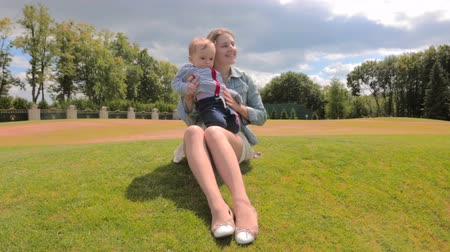 мама : Happy smiling mother relaxing with her baby boy on grass at park