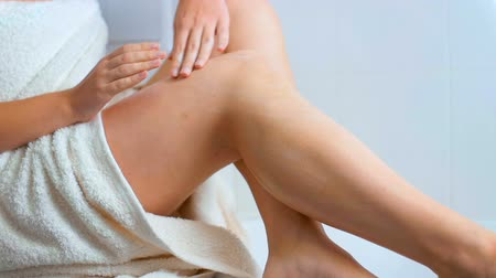 cuidados com o corpo : Slow motion video of sensual young woman applying lotion on legs at spa