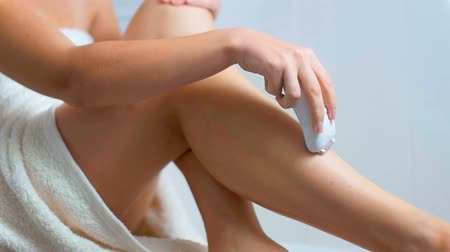 epilating : Closeup footage of young woman removing hair on legs with epilator at bathroom