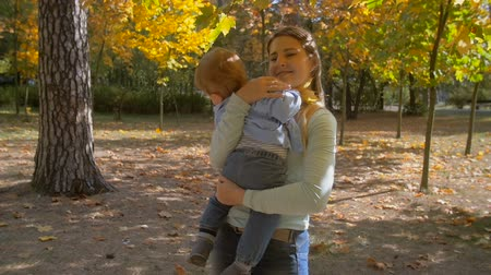 мама : Slow motion footage of beautiful caring mother embracing her baby son at autumn park under big tree