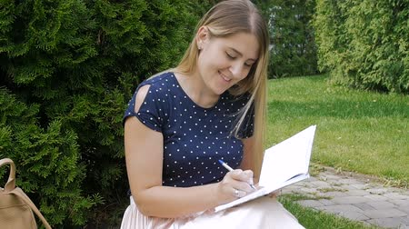 diary : . Slow motion footage of beautiful young woman sitting in park on grass and writing a diary Stock Footage