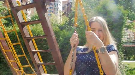 hravý : 4k video of beautiful smiling woman with long hair riding on swing at playground at park
