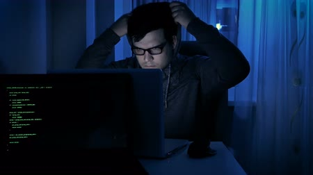 koncentracja : Footage of young man wearing hoodie and eyeglasses working at computer
