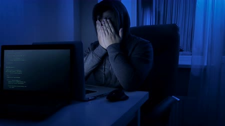 kraker : 4k footage of stressed man in hood working on laptop at home at night