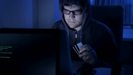 betrügen : 4k footage of hacker working at night. Man in hood stealing money from credit card Videos
