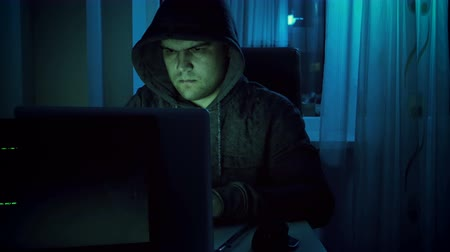 lopás : 4k footage of young male hacker in hoodie working on laptop at home in night. Concept of cyber crime
