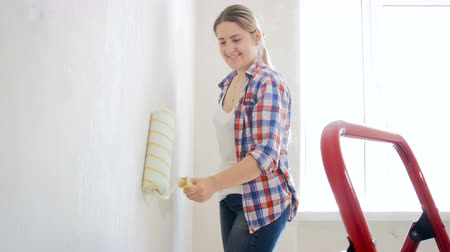 decorador : 4k footage of beautiful smiling woman painting wall with roller at new home Stock Footage