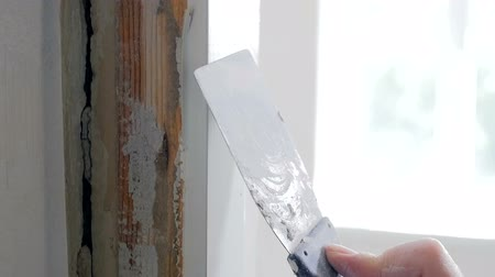 gondos : Closeup slow motion footage of hand holding spatula and removing old paint from wooden door Stock mozgókép