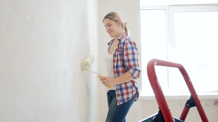 kutilství : Slow motion footage of beautiful young woman making renovation and painting walls