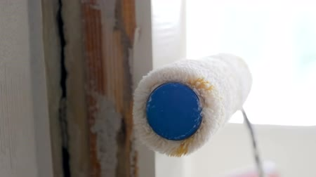 decorador : Closeup slow motion footage of paint roller rolling on wooden door