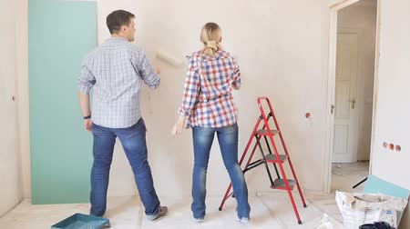в помещении : Slow motion footage of happy cheerful couple dancing while painting walls with paint roller at their new apartment under renovation