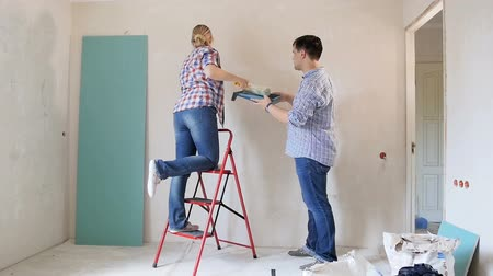 seçme : Cheerful young couple painting walls at their new home Stok Video