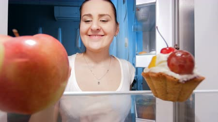 bezsennosć : 4k footage of young smiling woman taking red apple from refrigerator at night Wideo