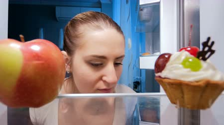 ataque : 4k footage of young woman looking for something to eat at night and taking fresh apple from refrigerator Vídeos