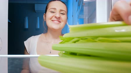 сельдерей : 4k footage of happy smiling woman taking and eating celery from refrigerator at night