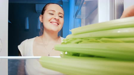 zeller : 4k footage of young beatiful woman taking and biting celery from refrigerator at night