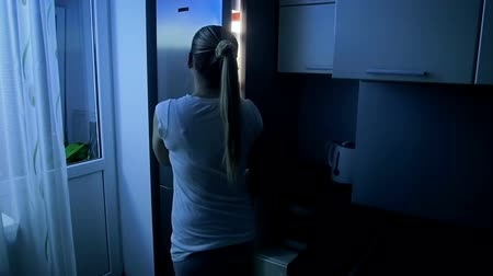 portaretrato : Slow motion footage of young woman open refrigerator at night Archivo de Video