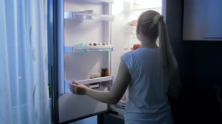 bezsennosć : Young woman feeling hungry at night opens refrigerator Wideo