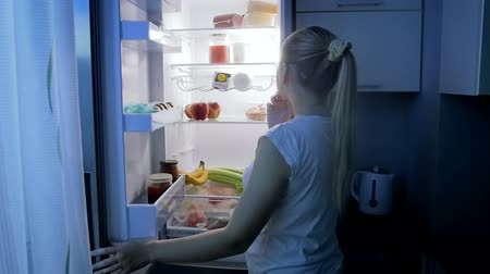 ataque : Young smiling woman taking food from refrigerator at night
