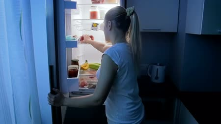 mrazák : Slow motion footafe of young sleepwalking woman taking food from refrigerator on kitchen