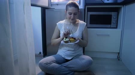 bulimia : Slow motion video of young woman in pajamas eating cake on floor at kitchen at night