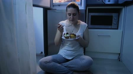 sitting floor : Slow motion video of young woman in pajamas eating cake at night. Concept of unhealthy nutrition and dieting