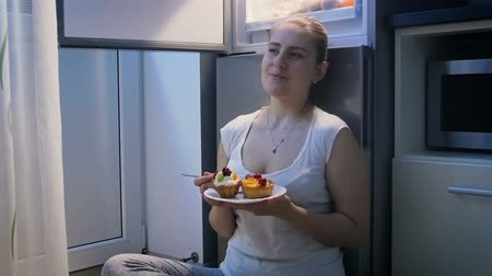 mrazák : Video of young woman sitting on floor at kitchen and eating sweet cake