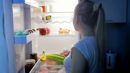 ataque : Young woman in pajamas takes out of refrigerator and eats apple at night Vídeos