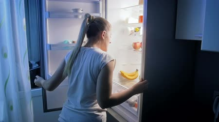 obżarstwo : Slow motion video of young woman looking for food in refrigerator at night