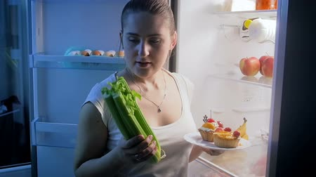 incerteza : Slow motion video of young woman choosing between vegetables and cake for late dinner