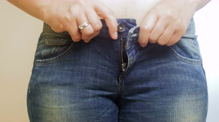 belly : 4k video of overweight woman struggling to put on her jeans Stock Footage