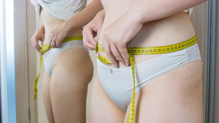 measure tape : 4k footage of obese woman measuring her waist at mirror Stock Footage