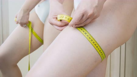 consciente : 4k video of young sexy woman measuring hips with yellow measuring tape