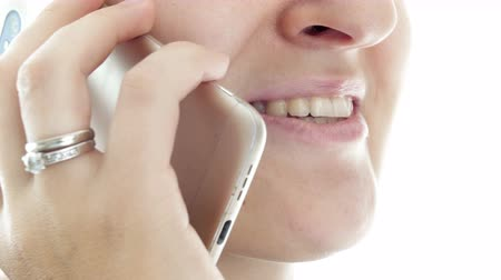 extreme close up : Extreme closeup video of young woman talking by phone and smiling
