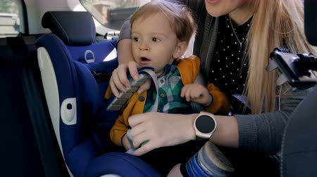 ofset : 4k footage of young mother fastening seat belts on her childs car seat