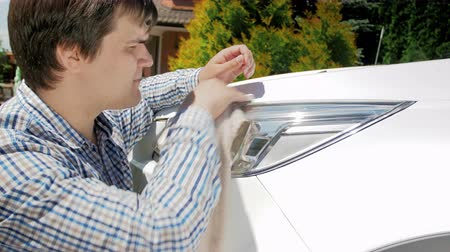 wiper : 4k video of young man polishing and cleaning car headlights with cloth