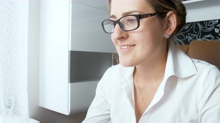 napirend : 4k closeup video of young smiling businesswoman wearing eyeglasses working at office and looking at computer screen Stock mozgókép