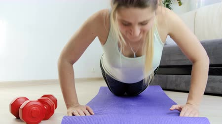 aerobic : 4k dolly footage of young woman with long hair doing push-ups on fitness mat at home