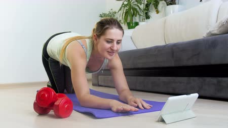 ped : 4k footage of beautiful young woman watching motivational video of digital tablet while exercising on fitness mat Stok Video